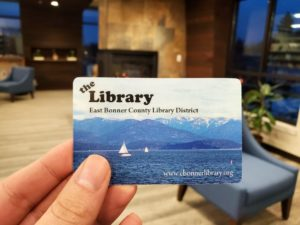 photo of hand holding a library card in front of the fireplace in the Sandpoint Library