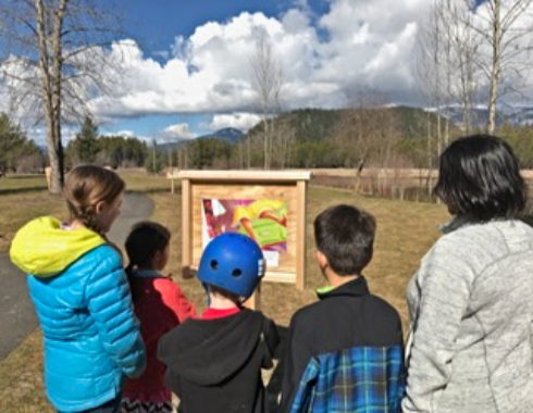 Photo of kids and adult reading a book page on a storywalk trail