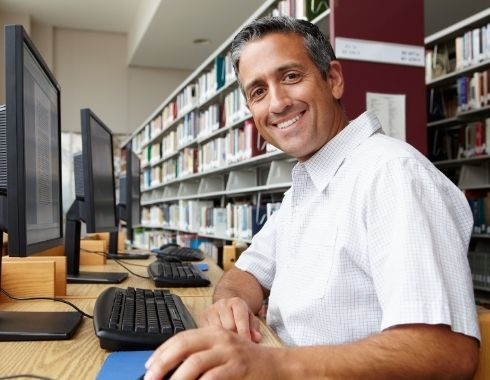 man using a public library computer, smiling at the camera