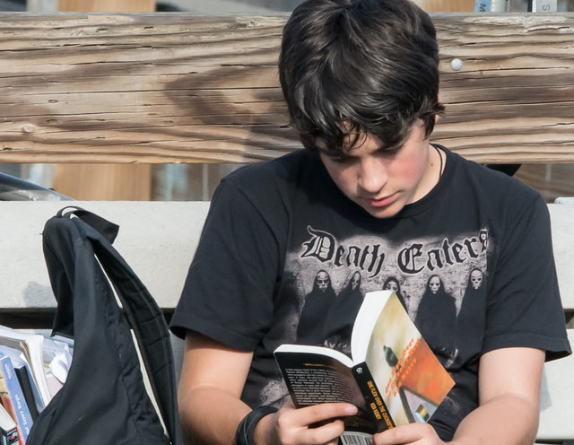 teen male reading a book next to backpack full of books