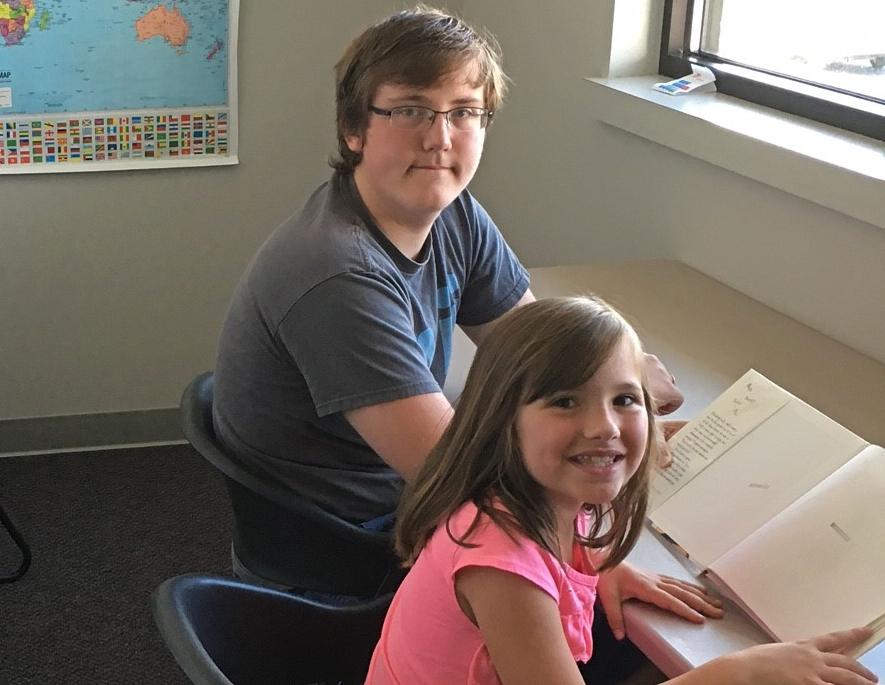 teen tutoring a child